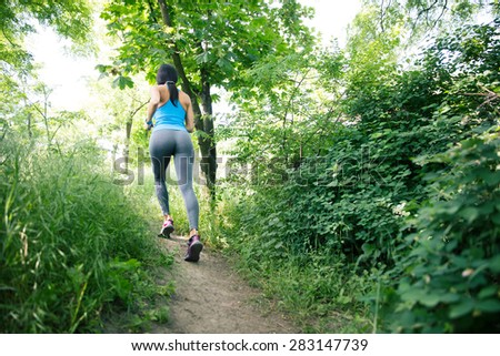 Back view portrait of a sporty woman running outdoors in park