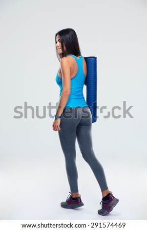 Back view portrait of a young fitness woman with yoga mat over gray background - stock photo