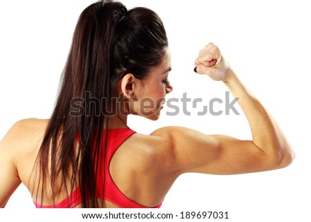 Back view portrait of a young sport woman looking at her biceps isolated on a white background