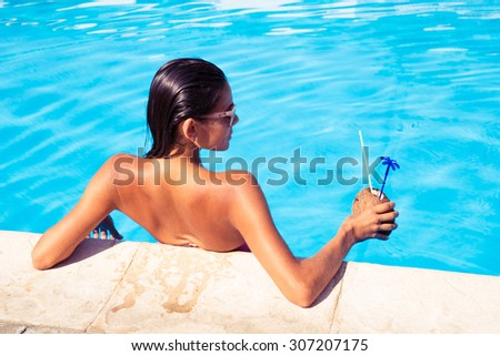 Back view portrait of a young woman standing in swim pool and holding cocktail in coconut outdoors