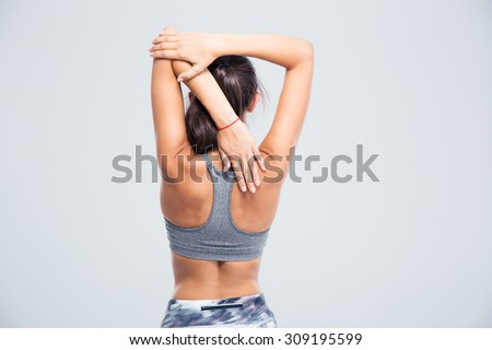 Back view portrait of a young woman stretching hands isolated on a white background - stock photo
