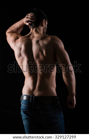 Back view portrait of athletic man with posing on black background