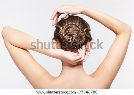 back view portrait of beautiful young dark blonde woman with creative braid hairdo on gray