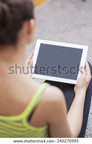 Back View Portrait of Woman Holding Tablet Computer. Focus on Tablet Computer. Vertical Image - stock photo
