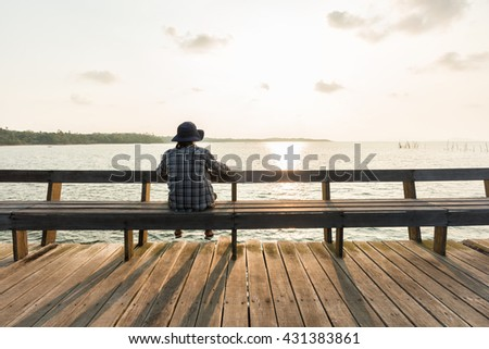 Back view portrait of young man sitting against the sea on wooden floor pier at sunrise time. - stock photo