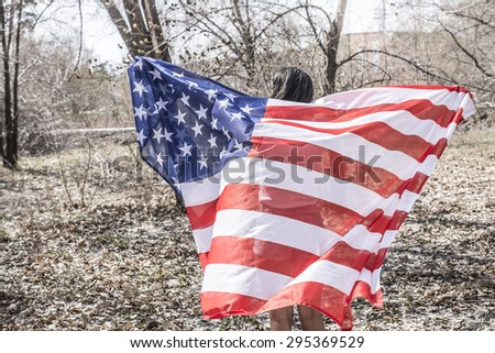 Back view Pretty girl wrapped in american flag smiling at camera on autumn or spring park background Cute woman wear stylish modern sunglasses on head against blue sky backdrop