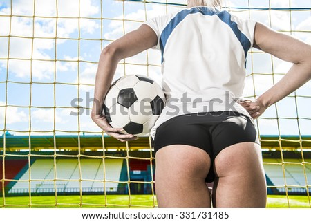 Back view. sexy Goalkeeper woman before a penalty kick. Empty stadium and blue sky with clouds on background. No face. Unrecognizable person. Space for inscription or objects. Big ass - stock photo