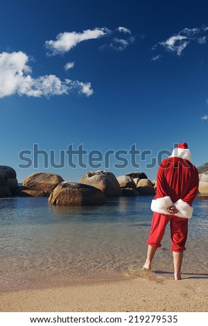 Back-view shot of Father Christmas standing on the beach and dipping his feet into the water of the calm sea with copyspace - stock photo