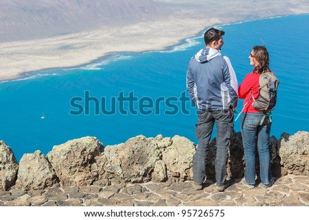 Back view sport couple with backpack standing on cliff's edge and looking to a island. - stock photo