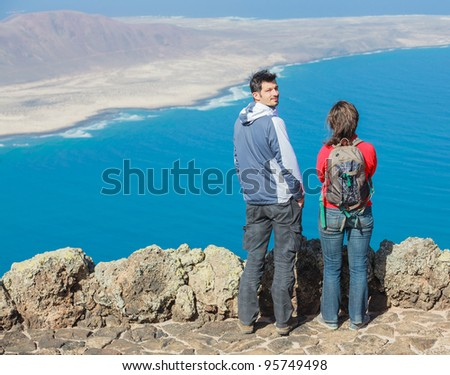Back view sport couple with backpack standing on cliff's edge and looking to a island.