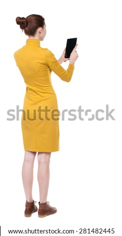 back view standing young beautiful  girl with tablet computer in hands. girl  watching.  backside view of person.  Isolated over white background. Girl in mustard strict dress looks into  tablet. - stock photo