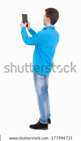 back view standing young man with tablet computer in the hands of. Rear view people collection.  backside view person.  Isolated over white background. guy in the blue sweater pictures of the tablet. - stock photo