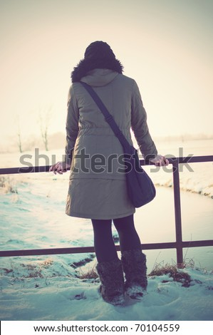 back view vintage portrait of young woman on a moat watching sunset in winter park - stock photo