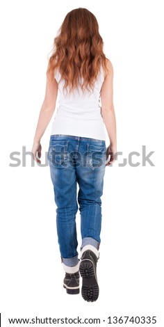 back view walking  leggy woman. beautiful redhead girl in motion. backside view person. Rear view people collection. Isolated over white background. trendy teen girl goes in mountain boots and jeans - stock photo
