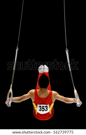 Back view with a gymnast performing on the rings apparatus - stock photo