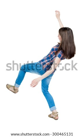 Back view woman Balances waving his arms.   Standing young girl in jeans. Rear view people collection.   A young girl in a checkered blue with red stripes and slipped trying not to fall. - stock photo
