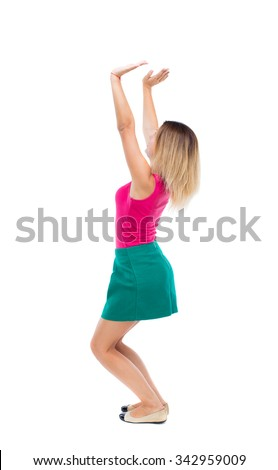 back view woman pushes wall.Isolated over white background. Rear view people collection. backside view person.blonde in a green skirt and pink blouse sitting down holding something heavy over his head