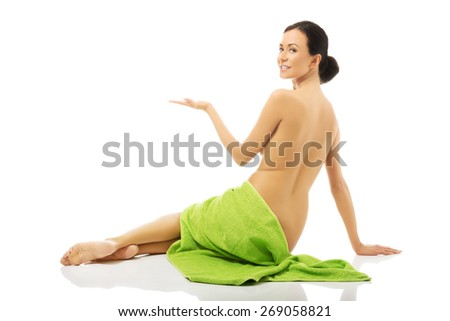 Back view woman wrapped in towel holding copyspace. - stock photo