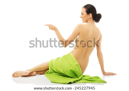 Back view woman wrapped in towel pointing left. - stock photo