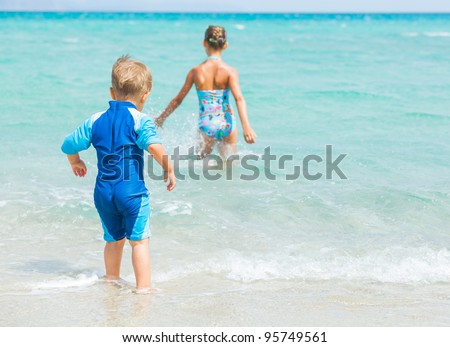 Back view young boy on sandy tropical beach, his sister background. - stock photo