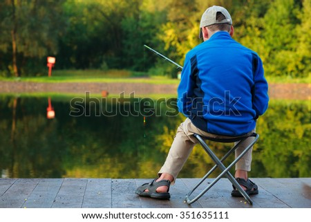 Back view young boy with fishing rod sitting on dock near lake.