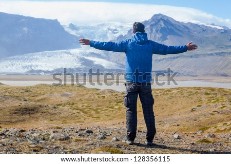 Back view young man enjoying the view Vatnajokull glacier. Iceland. - stock photo