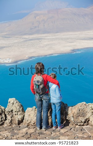 Back view young mother with backpack and daughter standing on cliff's edge and looking to a island. Vertical view - stock photo