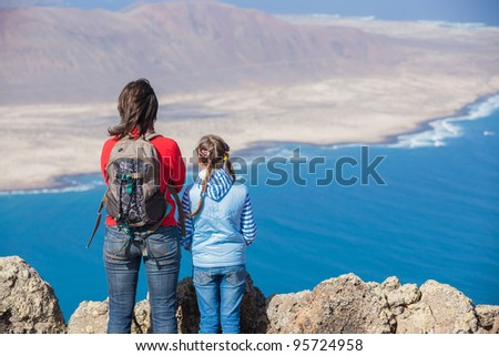 Back view young mother with backpack and daughter standing on cliff's edge and looking to a island. - stock photo