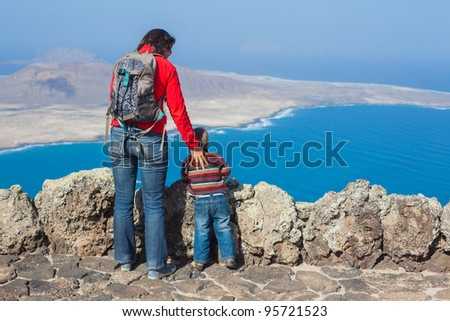 Back view young mother with backpack and son standing on cliff's edge and looking to a island. - stock photo
