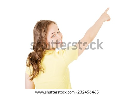 Back view young woman pointing up to the corner. - stock photo