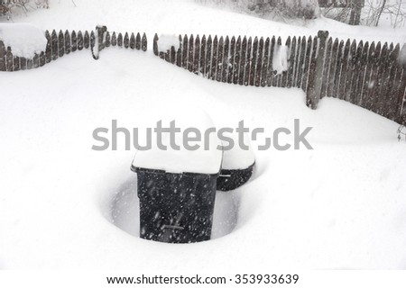 back yard fence and trash bin in blizzard - stock photo