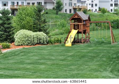 Back Yard Wooden Swing Set on Green Lawn - stock photo