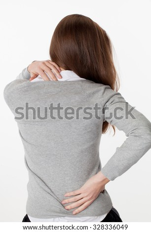 backache concept - young woman massaging her back from up and down for tension relief and posture relaxation,back view on white background - stock photo