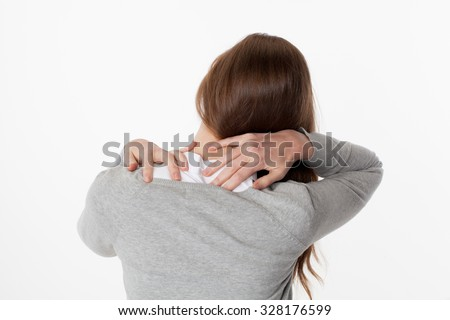 backache concept - young woman massaging her shoulders and neck for relief and posture relaxation,back view on white background - stock photo