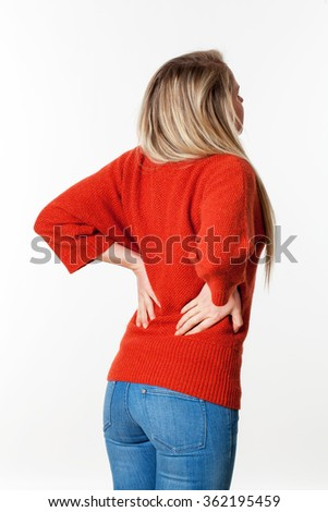 backache, lumbago, scoliosis health problems - young blond woman suffering from back pain, touching her lower vertebrae,white background