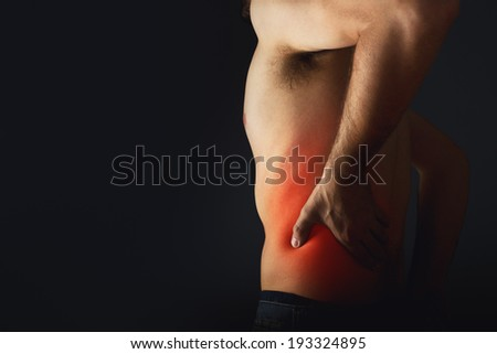 Backache. Pain in the lower back. Shirtless man touching his back for the pain. - stock photo