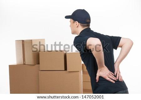 Backache. Young deliveryman standing with his hands on back and feeling pain - stock photo