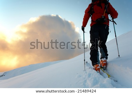 Backcountry skier walks in the snow at sunset, italian alps, europe.