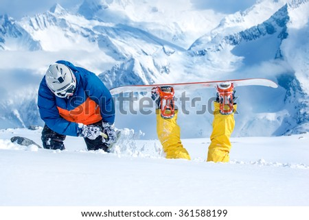 Backcountry snowboarder digging out his companion stuck in snow
