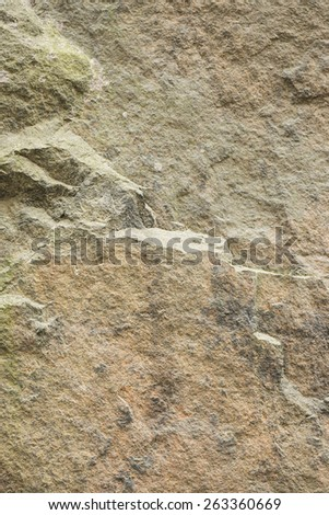 Backdrop of an old and weathered stone wall with rough texture. This vertical empty surface is perfect as copy space or textured background.  - stock photo