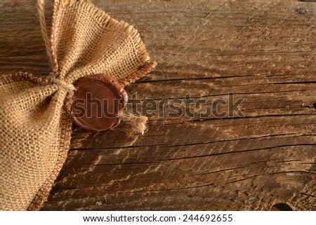 Backdrop of wax seal on sack cloth material on old retro vintage aged texture background Empty space for inscription  - stock photo