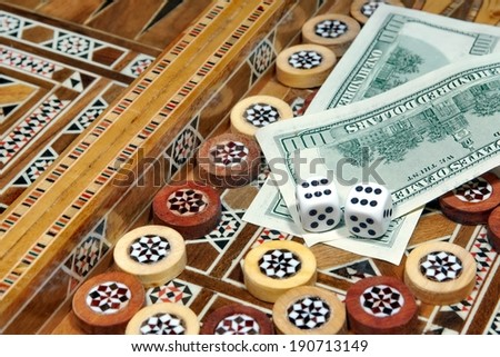 Backgammon Board and two hundred dollar as the prize for winning the game - stock photo