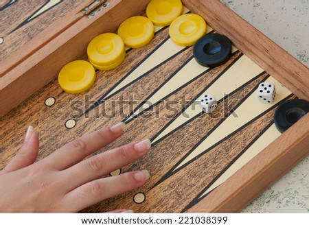 Backgammon game with hand throwing the dice. - stock photo