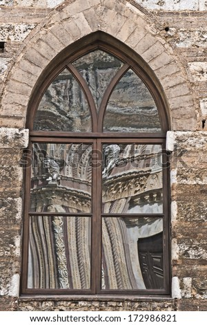 Background and a glass reflection of a typical Italian church, Italy
