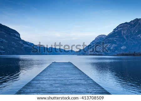 Background as epic mountain landscape.  Lake at sunset  with wooden pier. - stock photo