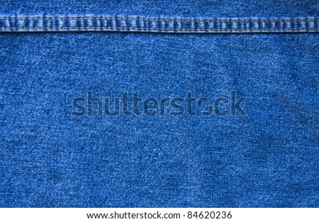 Background: blue denim with seam at the top of the frame - stock photo