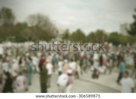 Background blur of crowd at political rally in the United States holding signs and carrying US flags for upcoming election cycle in 2016 presidential campaigns. Copy space. Vintage filter added. - stock photo