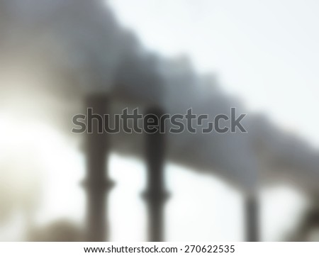 Background blur of factory chimneys billowing smoke with intentional light leak on left side  and filters applied. Useful for environmental issues, pollution, production and industrial concepts - stock photo