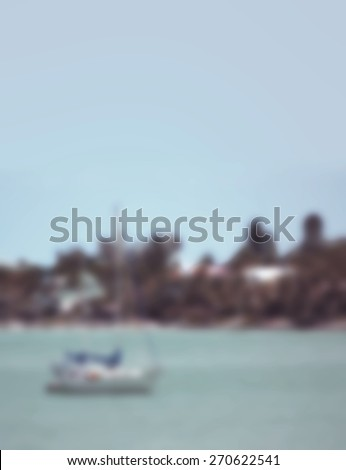 Background blur of sailboat moored near a shore with color filters applied for artistic purposes. The sailboat is to the left of the image. Sky and ocean or lake are blue. Trees and houses on shore. - stock photo