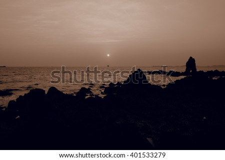 background blur sunset sea sky wave stone with gentle sepia tone
